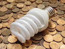 Energy saving light bulb on coins Royalty Free Stock Images