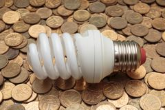 Energy saving light bulb on coins. Background royalty free stock photo