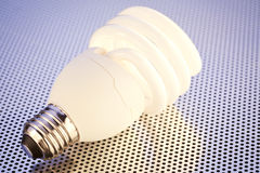 Energy Saving Light bulb. A compact fluorescent light bulb, also known as CFL over a metal background Royalty Free Stock Images