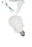 An energy saving light bulb falling into the water Royalty Free Stock Photos