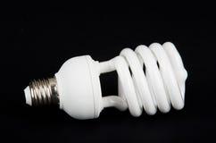 Energy saving light bulb. Energy saving fluorescent light bulb on black bakground Stock Photography