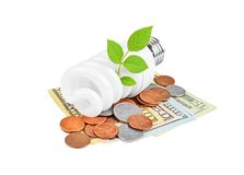 Energy saving light bulb, money and plant Stock Photos