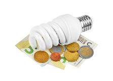 Energy saving light bulb and money Royalty Free Stock Image