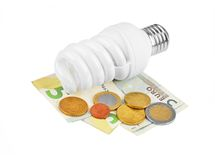 Energy saving light bulb and money Royalty Free Stock Images