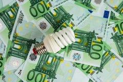 Free Energy Saving Light Bulb On Euro Stock Photography - 67689752