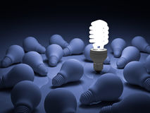Energy saving light bulb , one glowing compact fluorescent lightbulb standing out from unlit incandescent bulbs on blue. Background , individuality and Stock Image