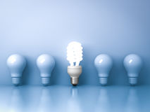 Energy saving light bulb , one glowing compact fluorescent lightbulb standing out from unlit incandescent bulbs on blue. Background , individuality and Stock Photo