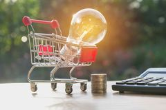 Energy saving light bulb with stacks of coins and shopping cart. For saving, financial and shopping concept Stock Photography