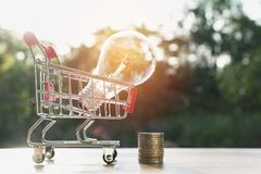 Energy saving light bulb with stacks of coins and shopping cart. For saving, financial and shopping concept Stock Image