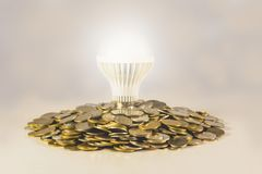Energy saving light bulb and surrounding by stacks of coins. Stock Photography