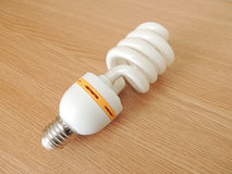 Energy saving light bulb. Energy saving light bulb on a wooden surface. Energy efficiency Royalty Free Stock Image