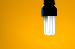 Yellow Light. An energy saving light bulb on a yellow background Royalty Free Stock Image