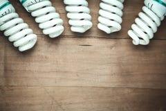 Energy saving light bulbs on wood background royalty free stock images