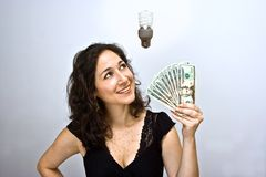 Energy saving money. Woman waving money and looking up. Having an environmentally friendly idea with an energy saving compact fluorescent light bulb floating stock image