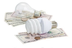Energy saving and normal   bulbs on dollars Stock Images