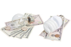 Energy saving and normal bulbs on dollars money. Energy saving and normal lamp bulbs on dollars money isolatd on white royalty free stock photos