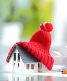 Energy saving Red Knitted Hat on Miniature House Royalty Free Stock Photo