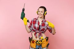 Energy sexy handyman woman in gloves, noise insulated headphones, kit tools belt full of instruments holding power. Electric drill isolated on pink background royalty free stock photo