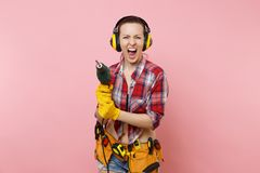 Energy sexy handyman woman in gloves, noise insulated headphones, kit tools belt full of instruments holding power. Electric drill isolated on pink background royalty free stock image