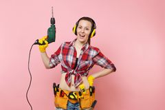 Energy handyman woman in gloves, noise insulated headphones, kit tools belt full of instruments holding power royalty free stock photos