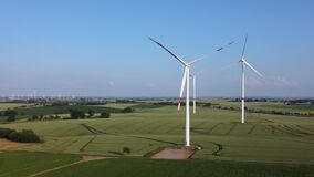 Wind turbines in an agricultural field on a summer afternoon.
