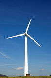 Energy wind turbine. On green grass with small house on bottom stock photos