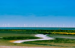 Energy wind turbine rotating fields at sunset Royalty Free Stock Images