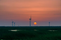 Energy wind turbine rotating fields at sunset. Wind energy as a clean, renewable energy, more and more attention around the world. Wind has long been use Stock Photos