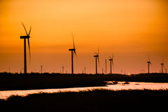 Energy wind turbine rotating fields at sunset Stock Images