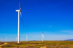 Energy Windmills In Open Field. Energy Producing Three Bladed Windmills In Open Field Against Blue Sky Background Royalty Free Stock Image