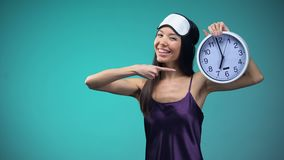 Energy woman in pajamas pointing at 7 am clock, wake up early, healthy lifestyle. Stock footage stock video footage