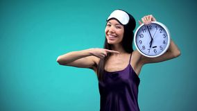 Energy woman in pajamas pointing at 7 am clock, wake up early, healthy lifestyle. Stock photo royalty free stock photo