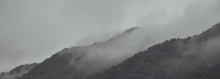 Enevoe através das montanhas como a pintura de paisagem chinesa Imagem de Stock