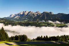 Enevoe no vale sobre Schladming, montanhas de Dachstein, cumes, Áustria fotografia de stock royalty free