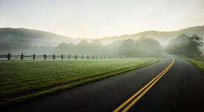 Enevoe o rolamento através das terras de exploração agrícola azuis da via pública larga e urbanizada do cume Foto de Stock
