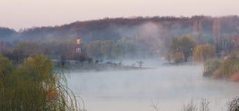 Enevoe sobre o lago, Corbeanca, o Condado de Ilfov, Romênia imagens de stock