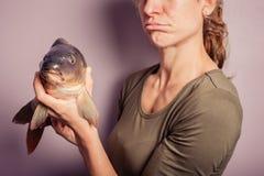 Enfaldig ung kvinna som poserar med en karp Royaltyfria Foton