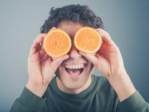 Enfaldig ung man som använder apelsiner som kikare Royaltyfri Bild