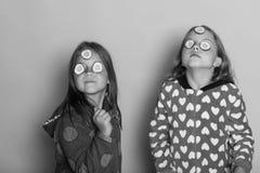 Enfance, amitié et concept de bonheur Enfants avec les visages sérieux, concombres sur des yeux et cheveux lâches Photographie stock