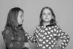 Enfance, amitié et concept de bonheur Pose d'enfants sur le fond rose Filles dans des pyjamas lumineux colorés Photo stock
