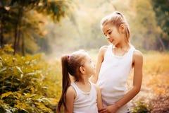 Enfance, famille, amitié et concept de personnes - deux soeurs heureuses d'enfants étreignant dehors Photographie stock