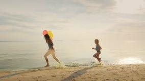 Enfance heureux - deux soeurs courant autour de l'un l'autre sur la plage Ayez l'amusement banque de vidéos