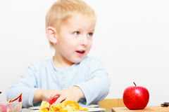 Enfance heureux. Enfant d'enfant de garçon mangeant du fruit épluché de pomme. À la maison. Image libre de droits