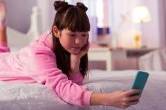 Enfant à cheveux longs attentif regardant l'écran de son instrument images stock