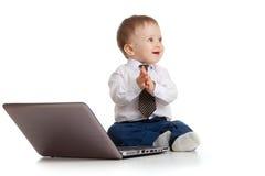 Enfant à l'aide d'un ordinateur portatif et battant ses mains Photos libres de droits