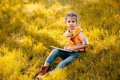 enfant à l'aide du comprimé numérique dans le parc image stock