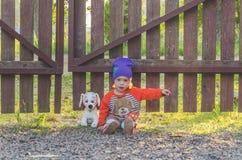 Enfant à la barrière, avec un chien de jouet Photographie stock