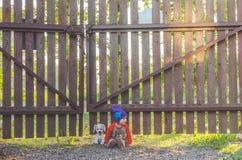 Enfant à la barrière, avec un chien de jouet Photos stock