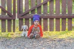 Enfant à la barrière, avec un chien de jouet Images stock
