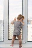 Enfant à la fenêtre Photos stock